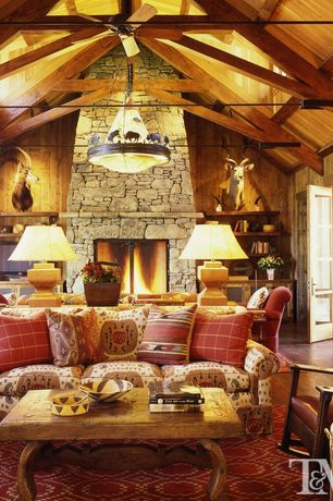 Rustic Living Room with Exposed trusses, L d burke of santa fe buffalo chandelier, French doors, stone fireplace, Wood walls