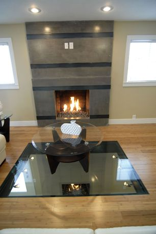 Modern Living Room with can lights, Standard height, Casement, Wall sconce, Laminate floors, Fireplace, insert fireplace