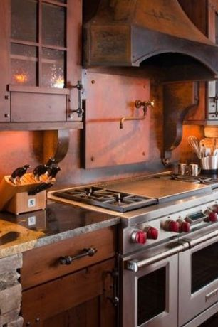 Eclectic Kitchen with Pot filler faucet, Interior stone facade, Copper vent hood, Interior stone wall