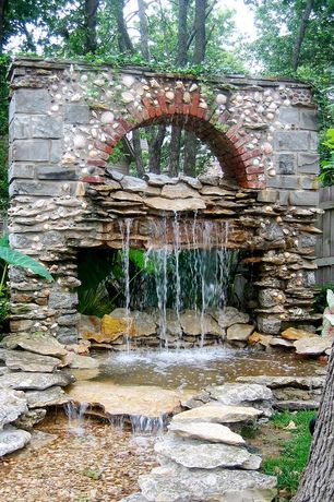 Traditional Landscape/Yard with exterior stone floors, Water feature, Fountain, White Queen Caladium, Pond, Fence
