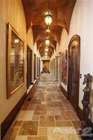 Mediterranean Hallway with Cathedral ceiling, Glass panel door, limestone floors, Pendant light