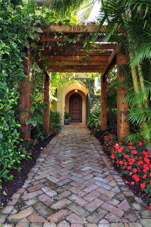 Tropical Landscape/Yard with Wood arbor, Tropical garden, Herringbone brick pattern, exterior brick floors, Pathway, Trellis