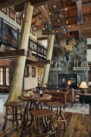 Rustic Great Room with Cathedral ceiling, Exposed beam, Hardwood floors, Loft, Columns, stone fireplace, Built-in bookshelf