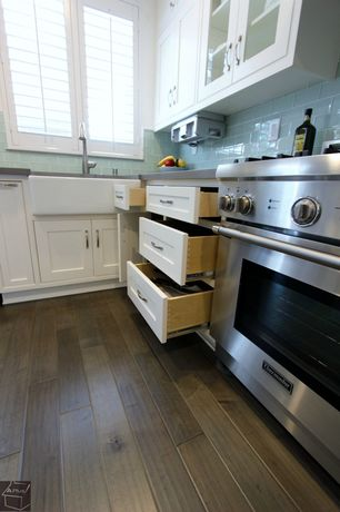 Kitchen with Plantation shutters, Walnut hardwood floors, Glass subway tiles, White cabinets, Farmhouse sink