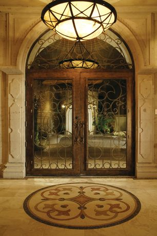 Mediterranean Entryway with sandstone floors, Chandelier, French doors, Crown molding, Arched window, High ceiling