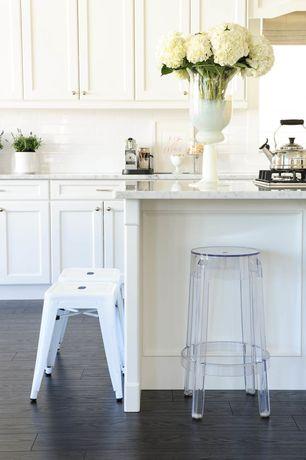 Traditional Kitchen with One-wall, Carrara marble countertop, Flat panel cabinets, Hardwood floors, Custom hood, Flush