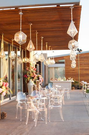 Contemporary Patio with Star diamond glass light pendant, Outdoor kitchen, Casper dining armchair in clear