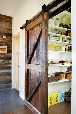 Country Pantry with Barn door, Hardwood floors, Daltile eci color body porcelain in city, Built-in bookshelf