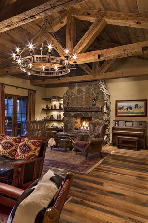 Rustic Great Room with Chandelier, French doors, Built-in bookshelf, stone fireplace, Hardwood floors, Exposed beam