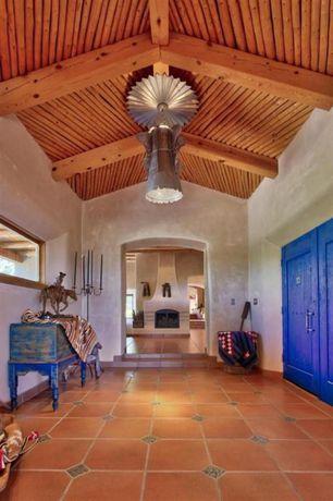 Mediterranean Entryway with Chandelier, terracotta tile floors, Exposed beam
