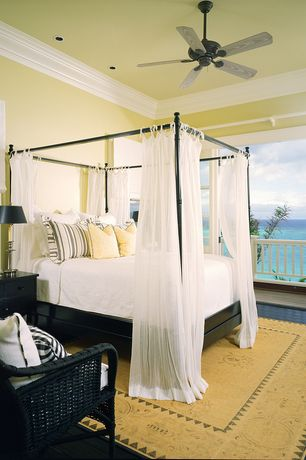 Tropical Guest Bedroom with Ceiling fan, Black wicker arm chair, Hardwood floors, Metal canopy bed, Crown molding