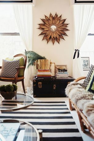 Eclectic Living Room with Horchow sunflower mirror, Crate & Barrel Olin Black 8'x10' Rug, Pole rattan sofa, Concrete floors