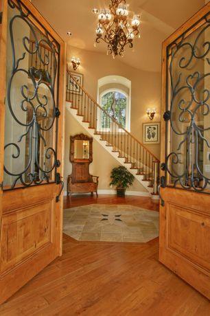 Mediterranean Entryway with Chandelier, French doors, Hardwood floors