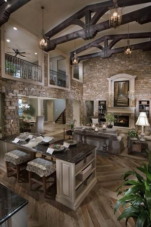 Rustic Great Room with Built-in bookshelf, Columns, Carpet, stone fireplace, Ceiling fan, High ceiling, Chandelier, Balcony