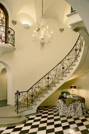 Traditional Staircase with Wall sconce, Concrete floors, High ceiling, Balcony, Chandelier, curved staircase