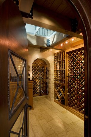 Mediterranean Wine Cellar with Exposed beam, Built-in bookshelf, Skylight, stone tile floors, flush light, High ceiling