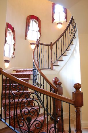 Mediterranean Staircase with Hardwood floors, Arched window, curved staircase, High ceiling, Wall sconce