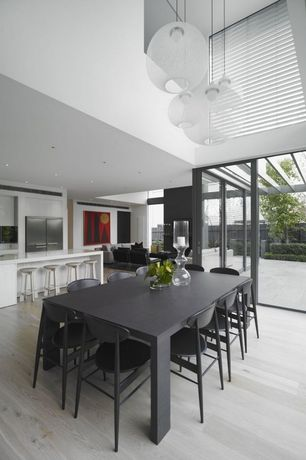 Contemporary Dining Room with Hardwood floors, Pendant light, French doors, High ceiling