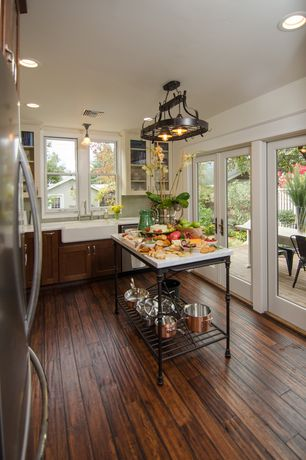 Country Kitchen with Corian counters, can lights, Farmhouse sink, full backsplash, Crate & barrel french kitchen island.