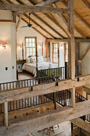 Rustic Master Bedroom with Exposed beam, Four poster bed, Hardwood floors, Exposed beam ceiling, Metal banister, High ceiling