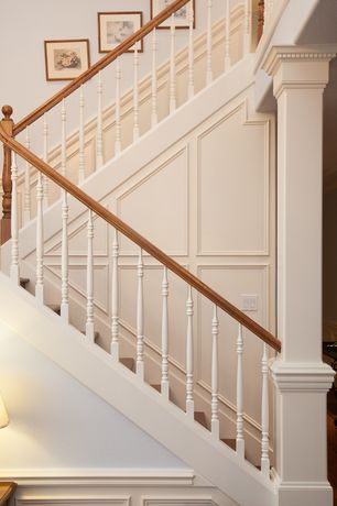 Traditional Staircase with High ceiling, curved staircase, Wainscotting, Hardwood floors, Columns
