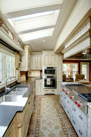 Country Kitchen with Solid surface countertop, U-shaped, Skylight, Raised panel, Brick backsplash, Kitchen island