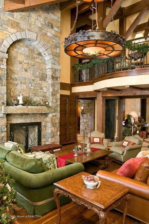 Eclectic Living Room with Hardwood floors, brick fireplace, six panel door, Exposed beam, High ceiling, Loft, Fireplace