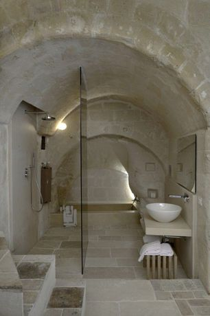 Eclectic Master Bathroom with Limestone, Vessel sink, Master bathroom, Handheld showerhead, Wall sconce, frameless showerdoor