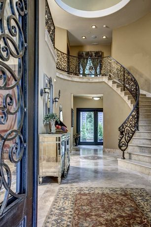 Traditional Entryway with French doors, travertine tile floors, High ceiling, Wall sconce, Mirrored three-drawer accent chest