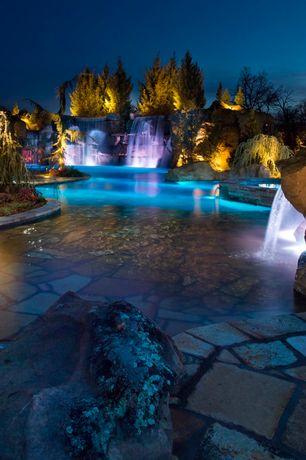 Rustic Swimming Pool with exterior stone floors, Grotto, Landscape lighting, Other Pool Type, Fence