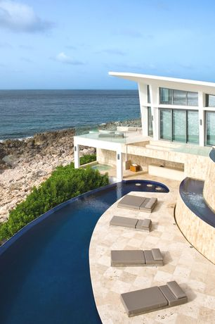 Modern Exterior of Home with exterior stone floors, Infinity pool