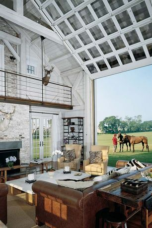 Traditional Living Room with Whitewashed brick, Loft, French doors, Taxidermy wall mounts, Exposed beam, Cathedral ceiling