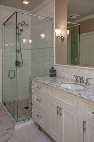 Traditional Master Bathroom with Wall sconce, Large Ceramic Tile, Handheld showerhead, Simple marble counters, Inset cabinets