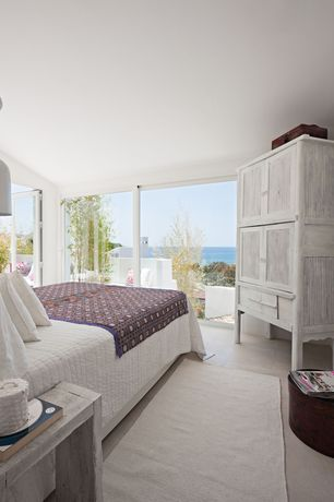 Tropical Master Bedroom with Built-in bookshelf, Concrete floors, sliding glass door, French doors, Pendant light