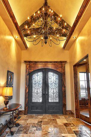 Mediterranean Entryway with High ceiling, French doors, Chandelier, travertine tile floors, Exposed beam, stone tile floors