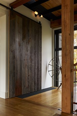 Country Entryway with High ceiling, Exposed beam, Columns, Hardwood floors, sliding glass door, Wood and iron, Wall sconce