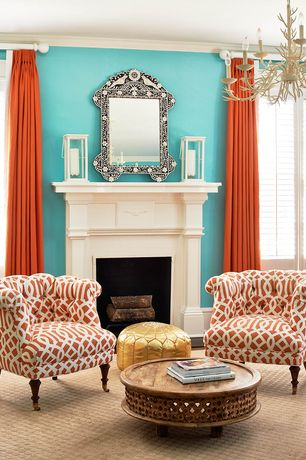 Eclectic Living Room with Cement fireplace, Paint, Chandelier, Hardwood floors, Orange curtain, Patterned arm chair