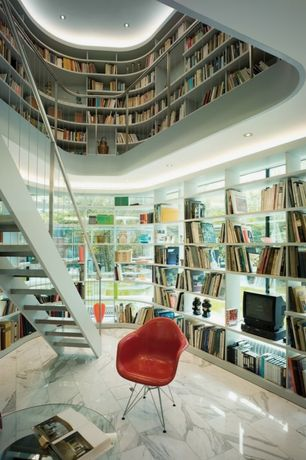 Contemporary Library with Herman Miller Eames Molded Fiberglass Wire-Base Armchair (DFAR), Built-in bookshelf, High ceiling