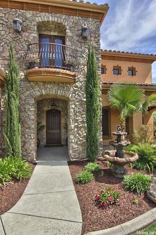 Mediterranean Exterior of Home with Fountain, exterior tile floors, French doors, Pathway