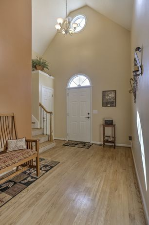 Traditional Entryway with Entry rug, Wall sconce, Transom window, Entry bench, Hardwood floors, Chandelier, High ceiling
