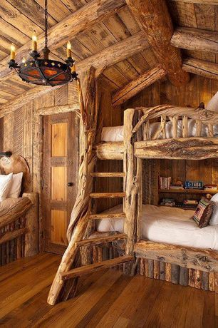 Rustic Guest Bedroom with Chandelier, specialty door, Exposed beam, Hardwood floors, Built-in bookshelf