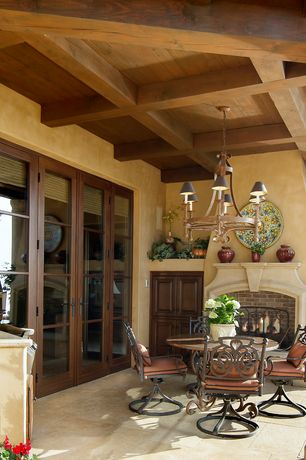 Mediterranean Patio with exterior tile floors, Outdoor fireplace, Chandelier, Faux finish paint, Coffered ceiling