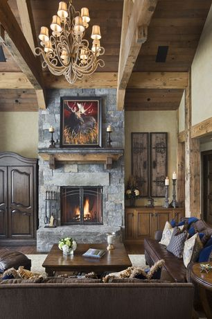 Rustic Living Room with Chandelier, Emerald pine square cocktail table, Hardwood floors, stone fireplace, Exposed beam