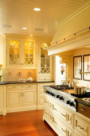 Traditional Kitchen with Raised panel cabinets, can lights, gas cooktop, Pot filler faucet, Custom hood, Glass panel cabinets