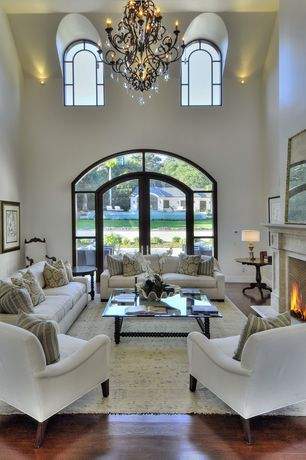 Eclectic Living Room with Cement fireplace, French doors, Chandelier, Cathedral ceiling, Arched window, Hardwood floors