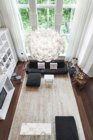 Modern Living Room with Hardwood floors, stone fireplace, High ceiling, Fireplace, Chandelier, Built-in bookshelf