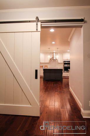 Country Hallway with Barn door, Crown molding, Paint, Hardwood floors