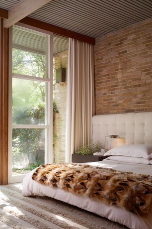 Contemporary Master Bedroom with Cost plus world market chocolate faux fur throw, High ceiling, interior brick, Exposed beam