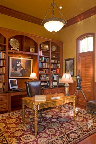 Traditional Home Office with specialty window, can lights, Standard height, Built-in bookshelf, Hardwood floors, Wainscotting
