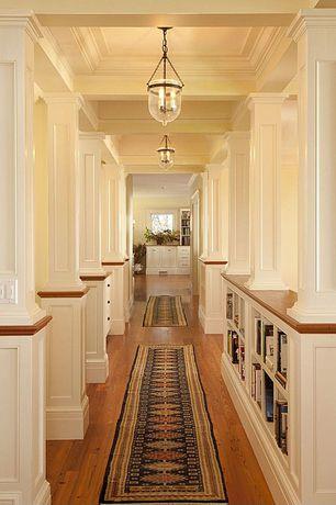 Hallway with Hardwood floors, Crown molding, Columns, Built-in bookshelf, Pendant light